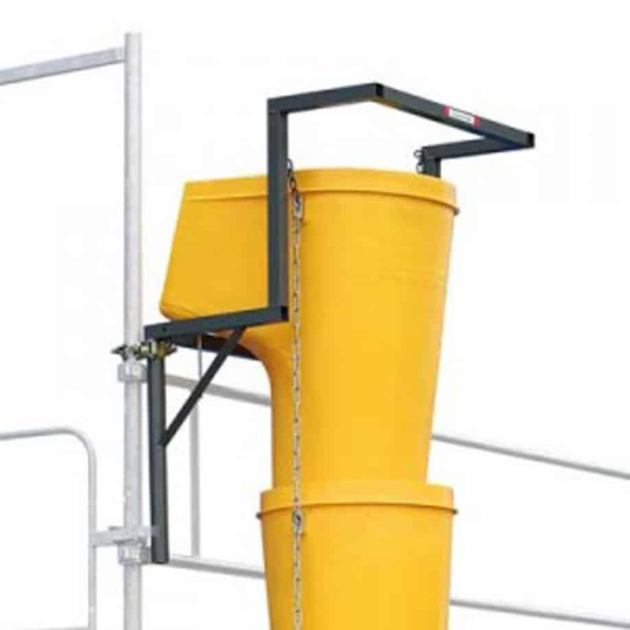 Показана е метална рамка захваната за скеле и към нея са съединени улеи за строителни отпадъци.