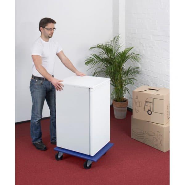 Мобилна поставка, правоъгълна синя . Показано е транспортиране на бяла техника по мокет.
