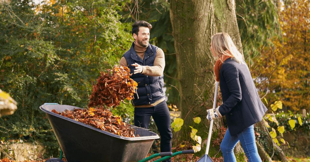 Двойка събира листа в ръчна количка с две колела