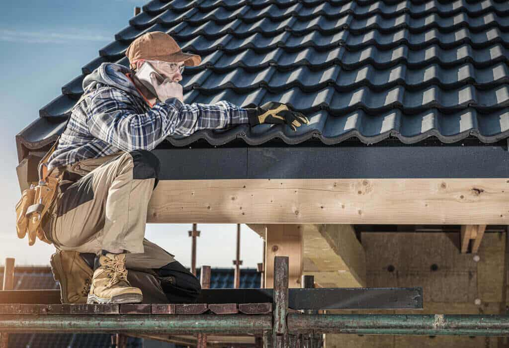 Работник говори по телефона на покрива